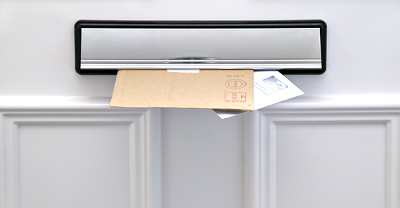 Image of mail dropping through a door mail slot.