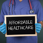 "Nurse holding a chalkboard sign with the phrase ""Affordable Healthcare"" written on it"