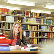 Young woman in higher education sitting at a desk in the library surrounded by schoolwork